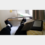 Im Krankenhaus Buchloe auf dem Bett lesend und die modischen Schuhe betrachtend.